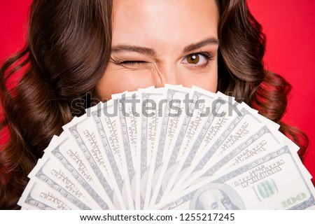 Close-up cropped portrait of rich funky attractive cheerful positive wavy-haired lady holding in hands hiding behind fan of hundreds usd dollars isolated over bright vivid shine red background