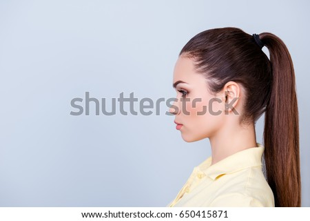 Close up cropped profile portrait of young lady in yellow tshirt with ponytail, serious face on pure background with copy space