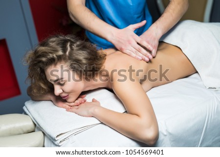 Close up cropped shot of a professional masseuse working massaging back of a woman relaxation pampering treatment beauty health lifestyle peace anti-stress relief #1054569401