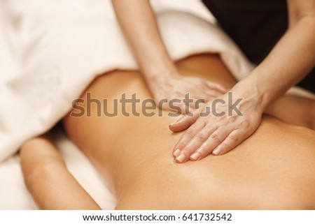 Close up cropped shot of a professional masseuse working massaging back of a woman relaxation pampering treatment beauty health lifestyle peace anti-stress relief job occupation professionalism skills #641732542