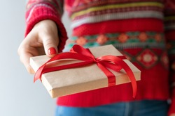 Close up cropped shot of woman hands with red polished nails holding gift box with red satin ribbon bow. European girl wearing red knitted sweater sharing present indoors. Focus is on the box.