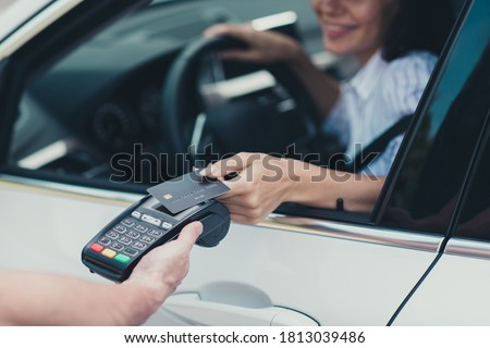 Close-up cropped view of her she attractive cheerful content busy successful lady customer consumer riding car paying virtual money using pay pass buying petrol goods product connection