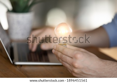 Close up cropped young man holding lighting bulb in hands, working on startup project on computer, having brilliant creative idea, feeling motivated and inspired at workplace, business success concept Foto stock ©