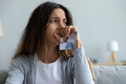 Close up crying woman holding torn picture of husband, break up with boyfriend or divorce, upset frustrated young female suffering from bad relationship problem, feeling lonely and depressed