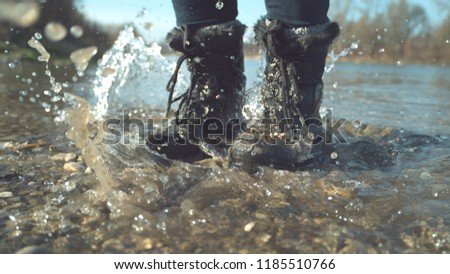 CLOSE UP: Crystal clear water splashes around unrecognizable playful girl's feet jumping around the refreshing stream in her fuzzy black boots. Cinematic shot of woman stomping her feet in the lake.