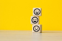 Close up custome choose smiley face and blurred sad face icon on wood cube, Service rating, satisfaction concept.