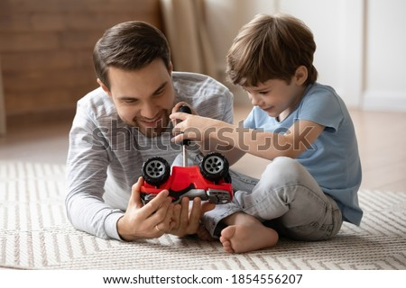 Close up cute adorable son repairing toy card with loving smiling father, playing on warm floor at home, little boy holding using screwdriver, having fun with dad, enjoying leisure time together