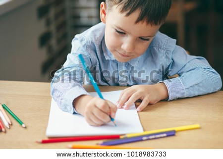Close-up, cute  boy doing homework,  coloring pages, writing and painting. Children paint. Kids draw. Preschooler with books at home. Preschoolers learn to write and read. Creative boy. #1018983733
