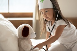 Close up cute curious Asian little girl wearing doctor uniform using stethoscope, sitting on cozy bed, pretty toddler child kid checking listening to toy heart beat, pretending pediatrician