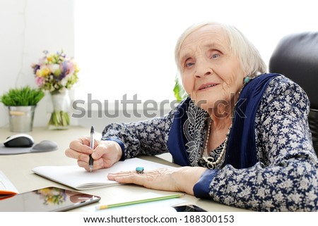 Close-up. Cute, elderly woman at the table