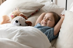 Close up cute little girl sleeping in bed with favorite fluffy toys, taking day nap, resting on soft pillows in cozy bed, adorable preschool kid relaxing in bedroom, healthy peaceful sleep