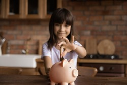 Close up cute smiling little girl putting coin into pink piggy bank, sitting at table in kitchen at home, adorable preschool child kid saving money for future, insurance and investment concept