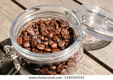 Close up dark brown roasted coffee beans in a glass jar in daylight