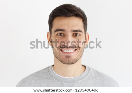Close-up daylight portrait of young smiling handsome man isolated on gray background Foto stock ©