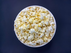Close up delicious fresh buttery popcorn in a bowl on dark blue background. Flat lay view