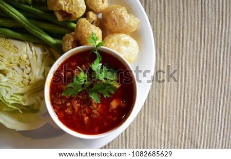 Close-up delicious looking Northern Thai minced pork and tomato spicy dip or Nam Prik Aong with healthy vegetables and pork rind on light fabric background with copy space for text #1082685629