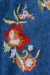 Close up denim embroidered flowers ,bird skirt jeans texture.