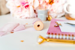 Close up Desktop handmade scrapbooking DIY tools. White working table background. Flat lay ribbons, tapes, peonies, golden paper binder clips, blank greeting card, Notebook and pen