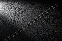 Close up detail black leather surface texture background with linear stiches. Part of leather chair