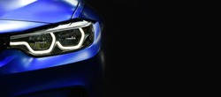 Close up detail blue modern car headlights with led technology on black background free space on right side for text.