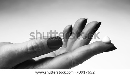 close up detail image of womans hand with red nails and a drop of hand cream