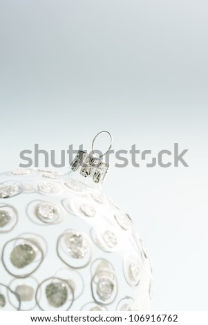 Close up detail of a Christmas ball ornament against a soft blue background.