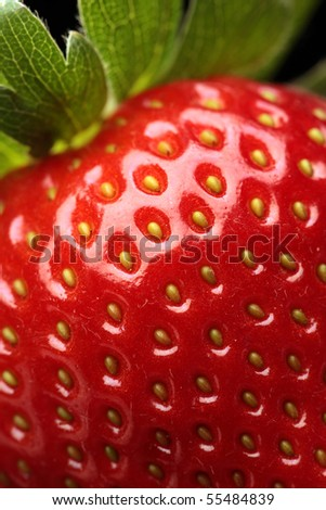Close-up detail of a fresh red strawberry with leaves