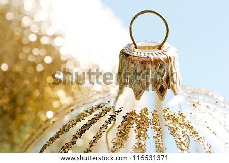 Close up detail of a pair of decorated christmas bar balls ornaments isolated against a blue background.