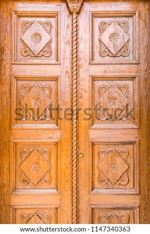 Close up detail of a wooden carved door with floral rhombus decorations #1147340363
