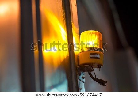 Close-up detail of a yellow revolving warning light shining onto a metal wall at a construction site. Industry and construction concept.