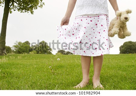 Close up detail of a young girl holding a soft toy in the park, body section.