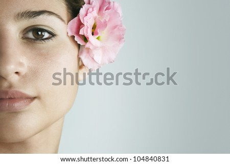 Close up detail of a young woman's half face wearing a tropical pink rose in her hair, on a plain background.