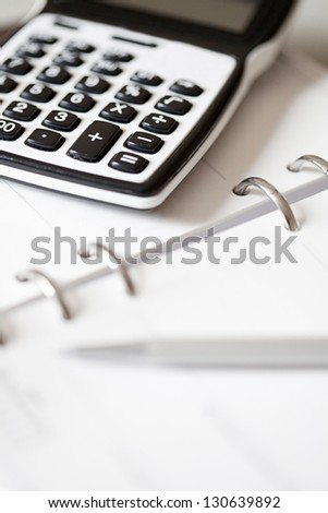 Close up detail of an open filofax week schedule with a silver pen and a maths calculator on it.