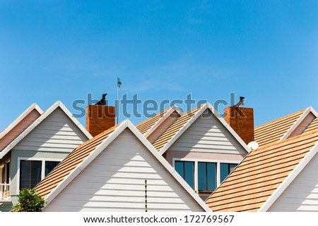 Close up detail of complex house rooftops against blue sky.