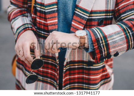 Close-up detail of fashion accessories, stylish young woman wearing an overcoat with a tartan pattern, a golden ring, a pair of modern sunglasses and a wrist watch.