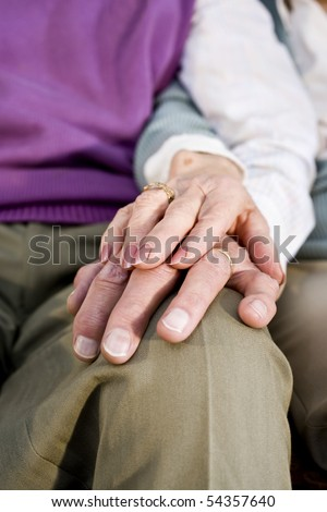 Close-up detail of hands of senior couple touching and resting on knee