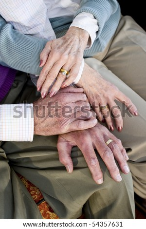 Close-up detail of hands of senior couple touching and resting on knees