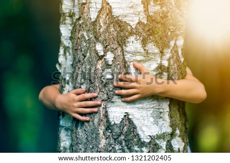 Close-up detail of isolated growing big strong tree trunk embraced from behind by small white child hands on blurred background. Love to nature, care for future and environment protection concept. #1321202405