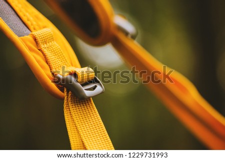 Close-up detail of locked black convenient plastic clasp of backpack yellow. #1229731993
