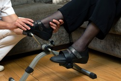 Close up detail of male therapist assisting senior woman's foot in stationary rehabilitation pedals.