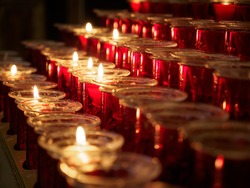 Close-up detail of multiple short candles in red holders lighting up a church. Valencia, Spain. Travel and religion concept.
