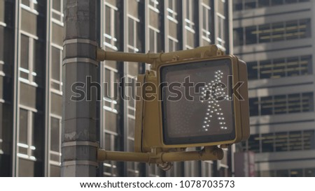 CLOSE UP: Detail of pedestrian crossing lights in New York City turning from signal with a little walking man indicating that it is safe to cross the road to red hand pictogram signaling don't cross #1078703573