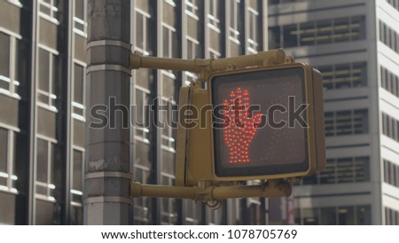 CLOSE UP: Detail of pedestrian crossing lights in New York City turning from signal with a little walking man indicating that it is safe to cross the road to red hand pictogram signaling don't cross #1078705769