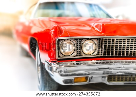 Close Up Detail of Shiny Red Classic Car with Focus on Headlights and Hood.