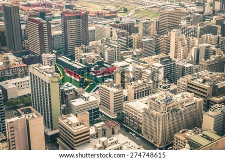 Close up detail of skyscrapers the business district of Johannesburg - Aerial view of modern buildings of the skyline in South Africa biggest city with southafrican flag painted on structure walls #274748615