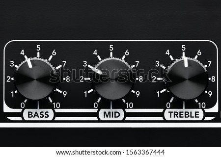 Close up detail of sound equalizer control knobs of a black guitar amplifier. Bass, mid and treble knobs.