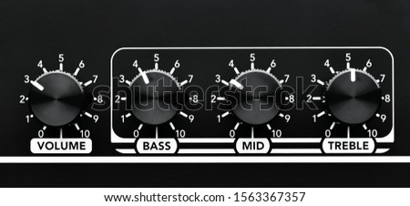 Close up detail of sound volume and equalizer control knobs of a black guitar amplifier