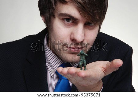 close up detail shot of business man playing with toy soldiers in his hand