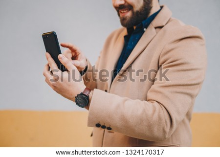 Close up detail shot of fashionable, young bearded man using his mobile phone, wearing men's camel chesterfield overcoat in front of a multicolored background. Space for text, copy, advertising.