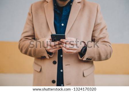 Close up detail shot of fashionable young man using his mobile phone, wearing men's chesterfield overcoat in camel color, in front of a multicolored background.